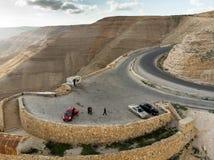 米底巴,约旦, 2018年3月10日:与三辆汽车的停车场和国王的Highway一个简单的报亭在旱谷Mujib Rese后 免版税库存图片