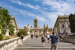 米开朗基罗台阶的游人对Piazza在Capitoline小山和Palazzo Senatorio,罗马,意大利顶部的del Campidoglio 免版税库存照片