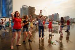 米斯克,比拉罗斯 跳舞在体育前面宫殿的雨中的青年人  免版税库存图片