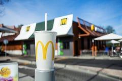 米斯克,白俄罗斯,可以18日2017年:在模糊的麦克唐纳` s餐馆背景的麦克唐纳` s软饮料纸杯 免版税库存图片