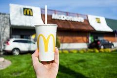 米斯克,白俄罗斯,可以18日2017年:麦克唐纳` s软饮料纸杯有模糊的麦克唐纳` s餐馆背景 库存图片