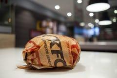 米斯克,白俄罗斯, 2018年3月27日:与肯德基商标的三明治在桌上在肯德基餐馆 库存照片