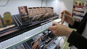 米斯克,白俄罗斯, 2018年6月2日:少妇在商店选择最大因素化妆用品 妇女使用构成测试器 股票视频