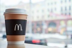 米斯克,白俄罗斯, 2018年2月18日:纸咖啡与麦克唐纳` s商标的在窗口附近的桌上在城市背景在麦克唐纳 免版税库存照片