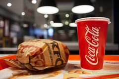 米斯克,白俄罗斯, 2018年3月27日:与肯德基商标的三明治和有可口可乐商标的纸杯在桌上在肯德基餐馆 图库摄影