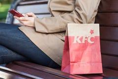 米斯克,白俄罗斯, 2017年6月21日:在一条长凳的午餐袋子肯德基在有一个手机的一名妇女旁边 库存照片
