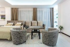 米斯克,白俄罗斯- 2019年1月:与电视沙发和扶手椅子的luxure大厅内部顶楼平的公寓 库存照片