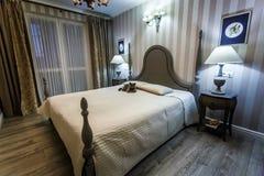 米斯克,白俄罗斯- 2019年2月:现代卧室的内部顶楼舱内甲板的在与英国猫的昂贵的公寓在床上 免版税库存照片