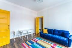 米斯克,白俄罗斯- 2019年3月:行家平的公寓减速火箭的明亮的内部与蓝色沙发、黄色门和色的地毯的 免版税图库摄影