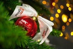 米斯克,白俄罗斯- 2017年11月20日:与商标垂悬从一棵装饰的圣诞树的肯德基的红色中看不中用的物品 库存图片
