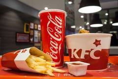 米斯克,白俄罗斯- 2017年10月30日:从鸡篮子,炸薯条,可口可乐吃午餐并且调味肯德基餐馆 图库摄影