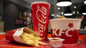 米斯克,白俄罗斯- 2017年10月30日:从鸡篮子,炸薯条,可口可乐吃午餐并且调味肯德基餐馆 影视素材