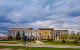 米斯克,白俄罗斯- 2018年5月01日:供以人员骑在独立的宫殿,总统住所前面的一辆自行车  库存图片