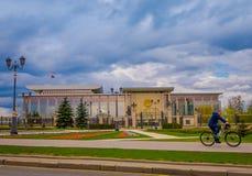 米斯克,白俄罗斯- 2018年5月01日:供以人员骑在独立的宫殿,总统住所前面的一辆自行车  免版税库存图片