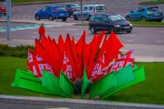 米斯克,白俄罗斯- 2018年5月01日:关闭红色和绿色旗子有被采取的城市风景的被弄脏的背景 免版税库存图片