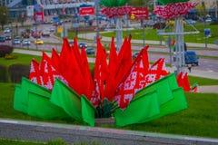米斯克,白俄罗斯- 2018年5月01日:关闭红色和绿色旗子有被采取的城市风景的被弄脏的背景 库存照片