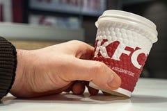 米斯克,白俄罗斯- 2017年11月28日:咖啡与商标肯德基的在手中在餐馆肯德基 库存图片