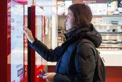 米斯克,白俄罗斯- 2017年11月26日:妇女使用肯德基报亭在肯德基餐馆点食物 免版税图库摄影