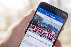 米斯克,白俄罗斯- 2018年4月14日:文章在叙利亚的没有战争是在euronews app的新闻在屏幕现代智能手机在人` s手上 库存图片