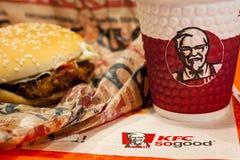米斯克,白俄罗斯- 2017年11月28日:汉堡和纸杯有肯德基商标的在盘子关闭在肯德基餐馆 免版税库存图片