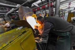 米斯克,白俄罗斯- 2018年2月01日:玻璃工人与在工厂背景玻璃的产业设备一起使用 免版税库存图片