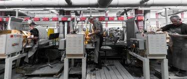 米斯克,白俄罗斯- 2018年2月01日:玻璃工人与在工厂背景玻璃的产业设备一起使用 库存照片