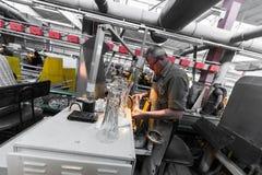 米斯克,白俄罗斯- 2018年2月01日:玻璃工人与在工厂背景玻璃的产业设备一起使用 图库摄影