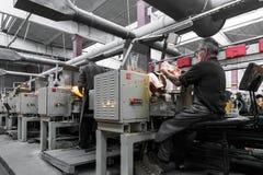 米斯克,白俄罗斯- 2018年2月01日:玻璃工人与在工厂背景玻璃的产业设备一起使用 免版税图库摄影