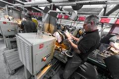 米斯克,白俄罗斯- 2018年2月01日:玻璃工人与在工厂背景玻璃的产业设备一起使用 库存图片