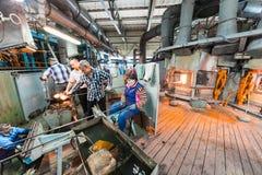 米斯克,白俄罗斯- 2018年2月01日:玻璃工人与在工厂背景的产业设备一起使用 库存照片