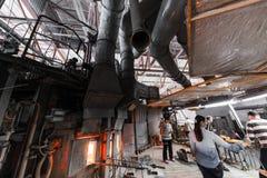 米斯克,白俄罗斯- 2018年2月01日:玻璃工人与在工厂背景的产业设备一起使用 图库摄影