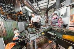 米斯克,白俄罗斯- 2018年2月01日:玻璃工人与在工厂背景的产业设备一起使用 免版税库存图片