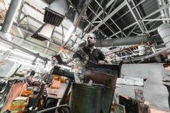 米斯克,白俄罗斯- 2018年2月01日:玻璃工人与在工厂背景的产业设备一起使用 免版税库存照片
