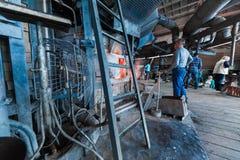 米斯克,白俄罗斯- 2018年2月01日:玻璃工人与在工厂背景的产业设备一起使用 免版税图库摄影