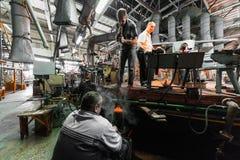 米斯克,白俄罗斯- 2018年2月01日:玻璃背景的生产的玻璃工厂劳工与制造一起使用 免版税图库摄影