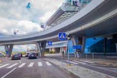 米斯克,白俄罗斯- 2018年5月01日:看法人走和汽车停放了在米斯克机场大厦输入在多云 免版税库存图片