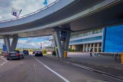 米斯克,白俄罗斯- 2018年5月01日:看法人走和汽车停放了在米斯克机场大厦输入在多云 免版税库存照片