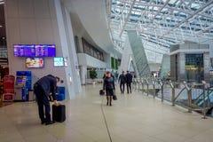 米斯克,白俄罗斯- 2018年5月01日:走与他们的行李和观看离开屏幕的未认出的游人,被找出 库存照片