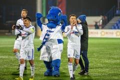 米斯克,白俄罗斯- 2018年3月31日:在白俄罗斯语英格兰足球超级联赛橄榄球期间,足球运动员和吉祥人庆祝目标 免版税库存照片