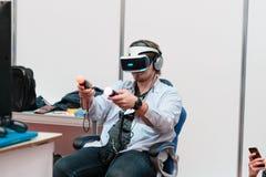 米斯克,白俄罗斯- 2017年4月18日:供以人员在虚拟现实耳机的尝试的戏剧在TIBO-2017第24个国际性组织专业论坛 免版税图库摄影