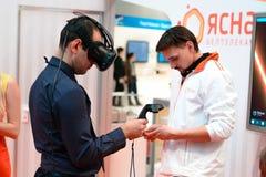 米斯克,白俄罗斯- 2017年4月18日:供以人员在虚拟现实耳机的尝试的戏剧在TIBO-2017第24个国际性组织专业论坛 免版税库存照片