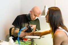 米斯克,白俄罗斯- 2015年9月19日:做在客户手上的专业艺术家纹身花刺 免版税图库摄影
