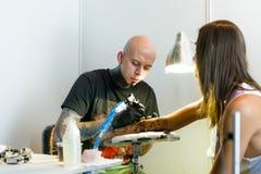 米斯克,白俄罗斯- 2015年9月19日:做在客户手上的专业艺术家纹身花刺 库存图片