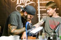 米斯克,白俄罗斯- 2015年9月19日:做在客户的专业艺术家纹身花刺 免版税库存照片