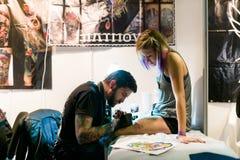 米斯克,白俄罗斯- 2015年9月19日:做在客户腿的专业艺术家纹身花刺 库存图片
