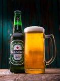 米斯克,白俄罗斯- 2017年1月05日:瓶海涅肯与玻璃的储藏啤酒在木桌和绿色背景上 生产Dutc 免版税库存图片