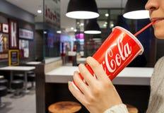 米斯克,白俄罗斯10月30日2017年:可口可乐软饮料 妇女喝在咖啡馆的可口可乐 免版税库存图片