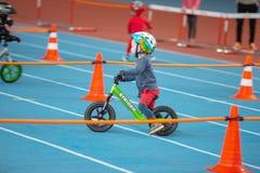 米斯克,白俄罗斯- 2月4 :盔甲乘驾平衡自行车和跑的自行车的柴尔兹在与父母的开放训练期间  免版税库存照片