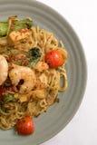 米氏goreng,油煎的黄色面条大虾海鲜菜蕃茄蛋大蒜青葱葱虾著名印度尼西亚辛辣料理 免版税图库摄影