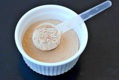 从米的植物蛋白粉末在白色碗的一个豌豆有在黑背景的塑料匙子的 库存图片